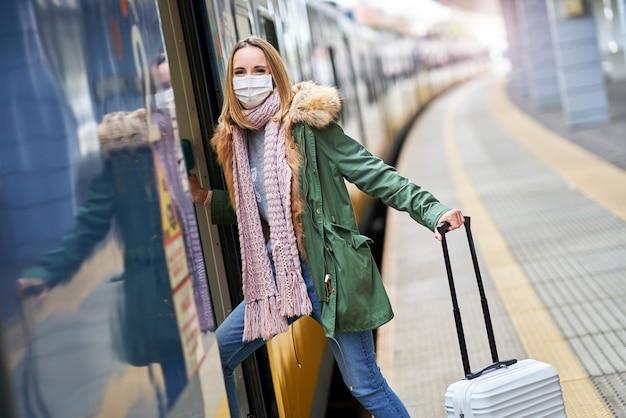 Femme adulte à la gare portant des masques en raison des restrictions de covid-19
