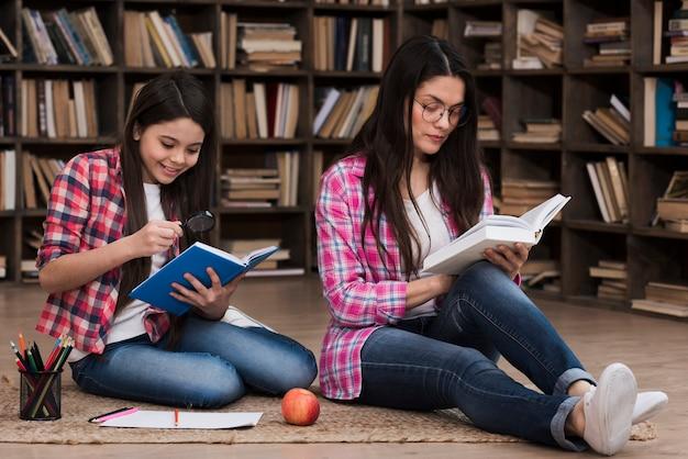 Femme adulte et jeune fille lisant ensemble