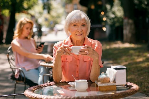 Femme adulte joyeuse assise à la table du café à l'extérieur avec une tasse de café