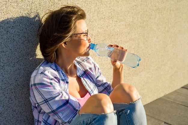 Femme adulte avec des lunettes boit de l'eau de bouteille