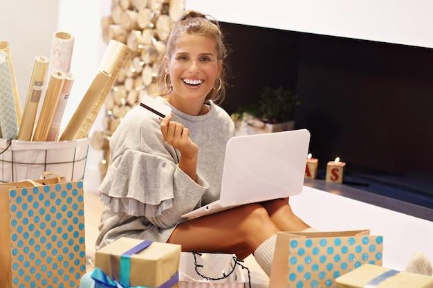 Femme adulte à la maison enveloppant des cadeaux de noël
