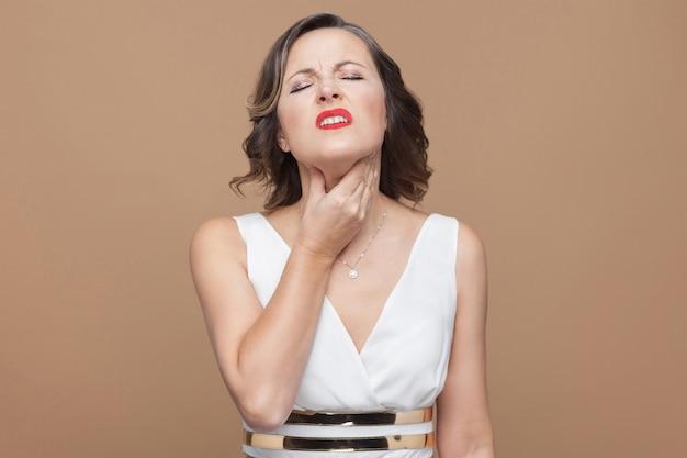 Une femme adulte a mal à la gorge. concept d'émotion et de sentiment. studio shot, intérieur, isolé sur fond marron clair