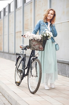 Femme adulte marchant avec le vélo urbain
