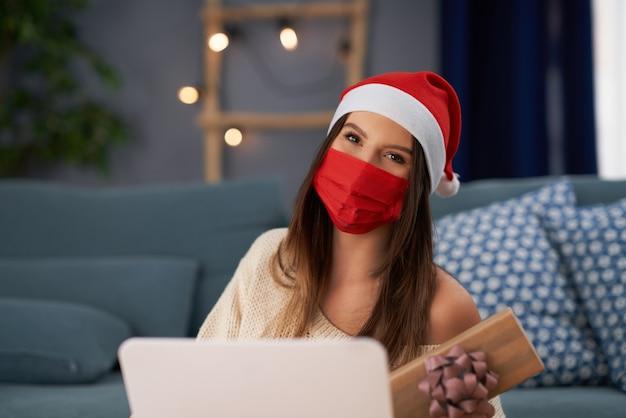 Femme adulte avec masque célébrant noël à la maison et faisant un appel vidéo avec des amis