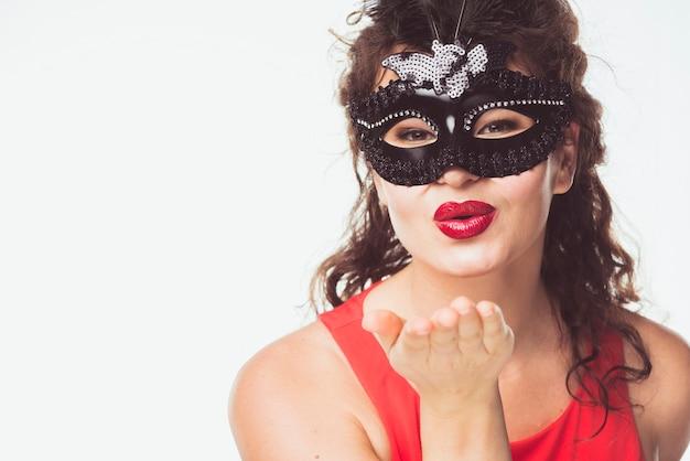 Femme adulte en masque envoyant un baiser d'air