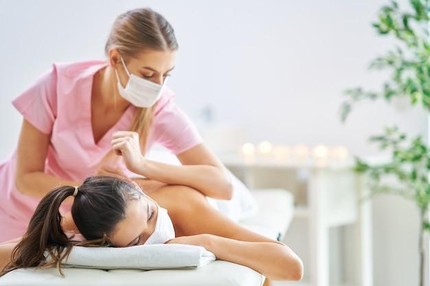 Femme adulte en masque lors d'un massage relaxant au spa