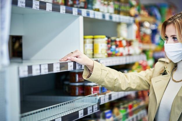 Femme adulte en masque médical devant des étagères vides dans une épicerie