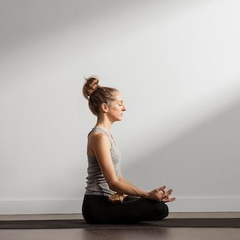 Femme adulte méditant à la maison