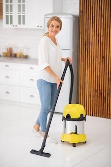 Femme adulte mince souriante avec aspirateur debout dans une cuisine légère à la maison