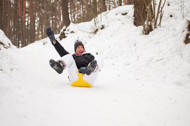Une femme adulte monte sur un traîneau à glace depuis une montagne escarpée. plaisir d'hiver. pour n'importe quel but.