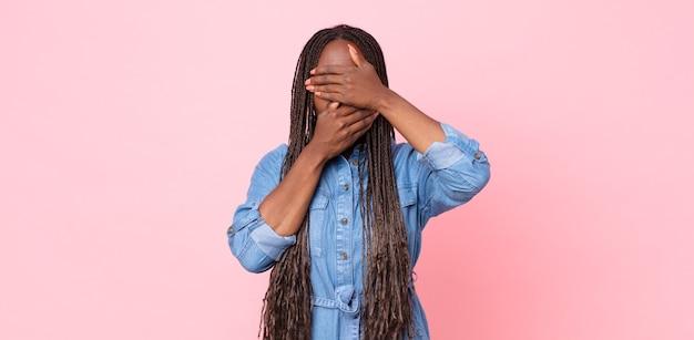 Femme adulte noire afro couvrant le visage avec les deux mains disant non à la caméra ! refuser des photos ou interdire des photos