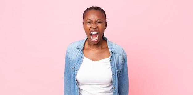 Femme adulte noire afro criant agressivement, ayant l'air très en colère, frustrée, indignée ou agacée, criant non