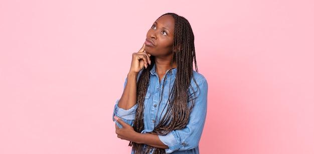 Femme adulte noire afro avec un regard concentré, se demandant avec une expression douteuse, regardant vers le haut et sur le côté