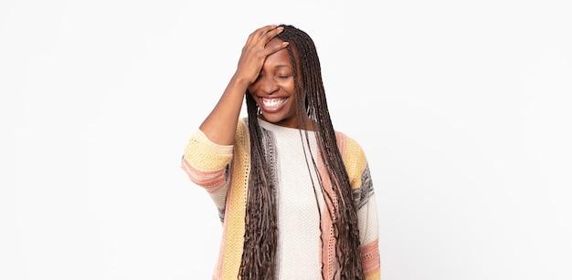 Femme adulte noire afro riant et giflant le front comme disant dã¢â€â™oh! j'ai oublié ou c'était une erreur stupide