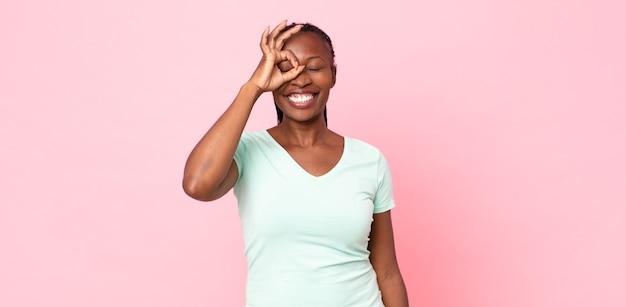 Femme adulte noire afro souriante joyeusement avec une grimace, plaisantant et regardant à travers le judas, espionnant les secrets