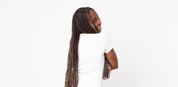 Femme adulte noire afro souriante joyeusement, se sentant heureuse, satisfaite et détendue, les bras croisés et regardant sur le côté