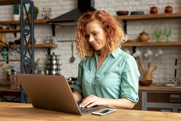 Femme adulte avec un ordinateur portable dans la cuisine