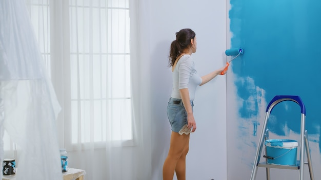 Femme adulte peignant le mur à l'aide d'une brosse à rouleau trempée dans de la peinture bleue. concepteur de maison rénover, rénover. redécoration d'appartements et construction de maisons tout en rénovant et en améliorant. réparation et décoration