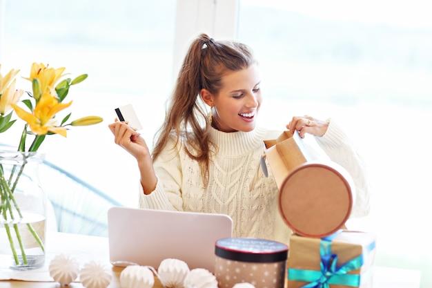Femme adulte portant un chandail chaud et faisant des achats en ligne à l'époque de noël