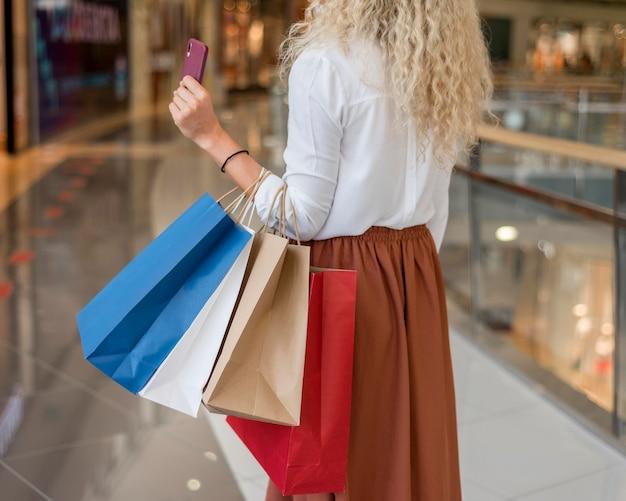 Femme adulte portant des sacs à provisions au centre commercial