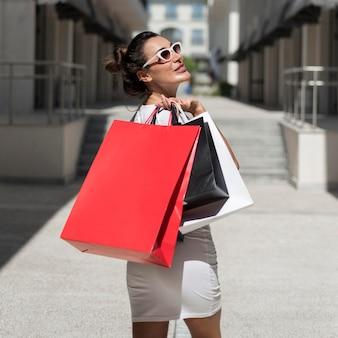 Femme adulte posant avec des sacs à provisions