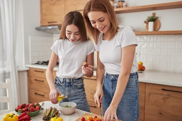 Femme adulte positive avec une fille préadolescente préparant un repas végétarien sain avec des ingrédients frais dans la cuisine à domicile