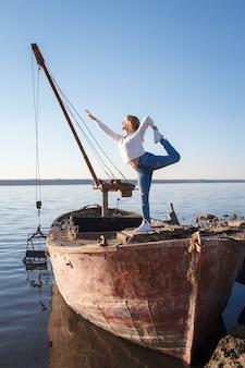 Femme adulte pratique le yoga sur un vieux bateau sur la plage