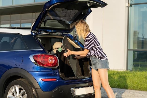 Une femme adulte prend le longboard du coffre de la voiture femme de s au parking pour faire de la planche à roulettes le week-end d'été