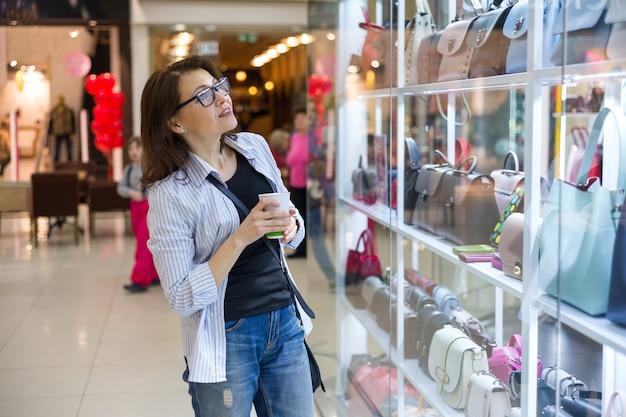 Femme adulte en regardant la vitrine avec des sacs