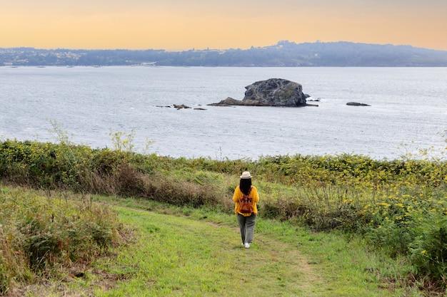 Une femme adulte avec un sac à dos en cuir descend un chemin près de la côte