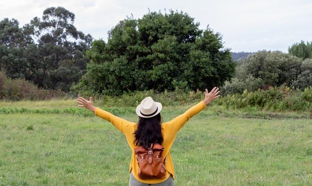 Une femme adulte avec un sac à dos en cuir descend le chemin