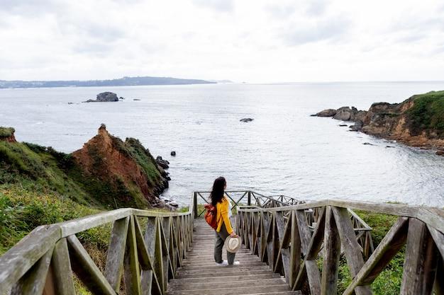 Femme adulte avec un sac à dos en cuir près de la côte