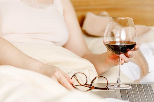 Femme adulte se détendre dans son lit avec un verre de vin rouge et l'ordinateur portable