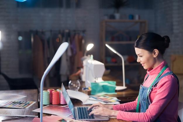 Une femme adulte tape sur un ordinateur.