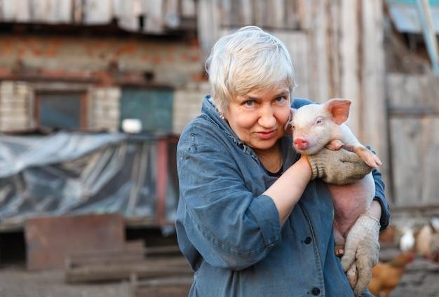 Femme adulte tenant un petit cochon et regardant la caméra
