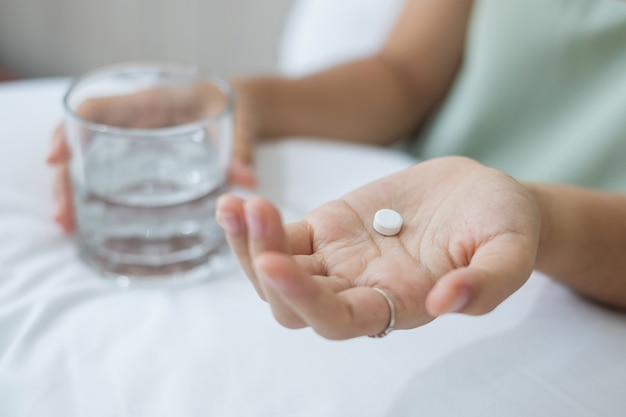 Femme adulte tenant une pilule et un verre d'eau, prenant des médicaments sur le lit le matin à la maison. concept de migraine, analgésique, maux de tête, grippe, maladie, maladie et soins de santé