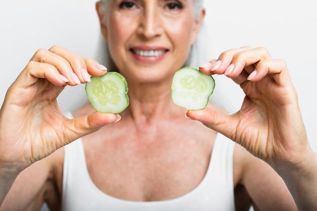 Femme adulte tenant des tranches de concombre