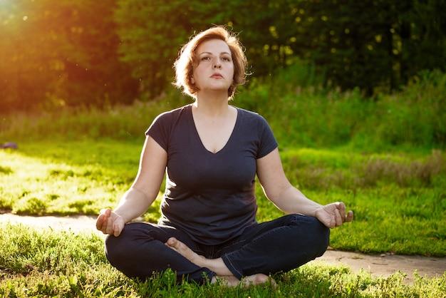 Une femme adulte en vêtements sombres en position du lotus médite dans le parc dans les rayons du soleil