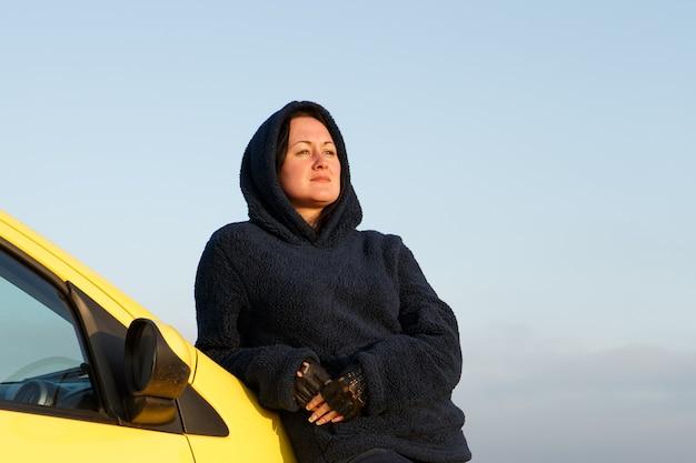 Une femme adulte vêtue d'une veste chaude parcourt en voiture les lieux de la nature en toute liberté...