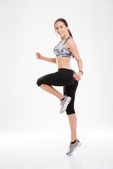 Femme aérobie pleine longueur dansant en studio. se tient de côté.