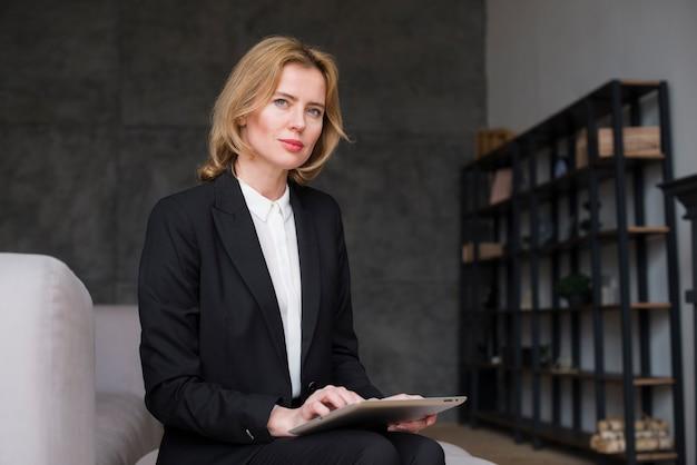 Femme d'affaire blonde réfléchie assise avec tablette