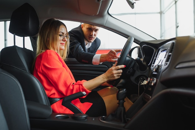 Femme d'affaires achète une voiture chez un concessionnaire automobile.