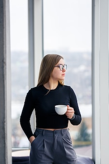 Femme d'affaires adulte professionnelle buvant du café en chemise et pantalon debout devant de grandes baies vitrées.