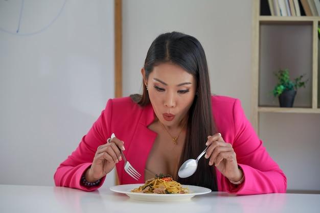 Une femme d'affaires affamée regarde une assiette de pâtes à spaghetti et une fourchette mangeant furieusement des pâtes. homme d'affaires ou employé de bureau mangeant de la nourriture italienne pendant la pause déjeuner.