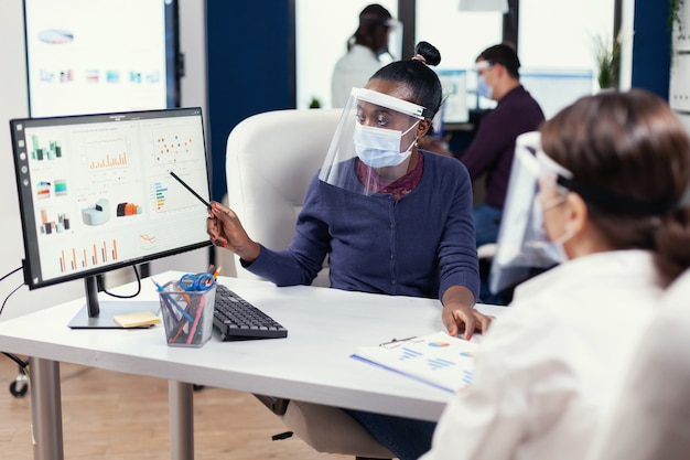 Femme d'affaires africaine analysant un graphique coloré au bureau portant un masque facial. équipe multiethnique travaillant en entreprise avec une nouvelle norme respectant la distance sociale en raison de la pandémie mondiale de coronavirus.