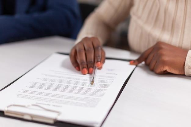 Femme d'affaires africaine lisant des documents de signature