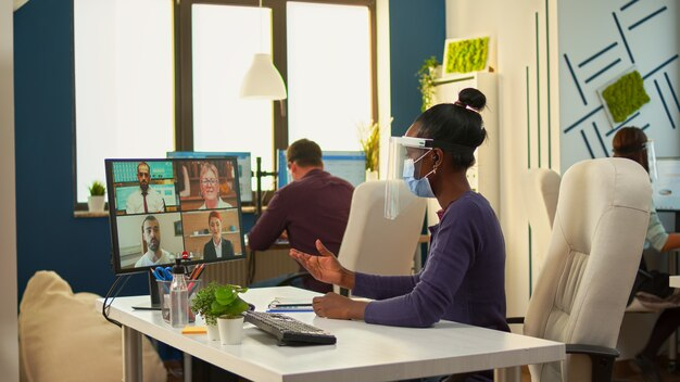 Femme d'affaires africaine avec masque facial au bureau parlant en appel vidéo avec une équipe à distance pendant l'épidémie de coronavirus. avoir une conférence en ligne, rencontrer des collègues en vidéo travaillant dans le respect de la distance sociale.