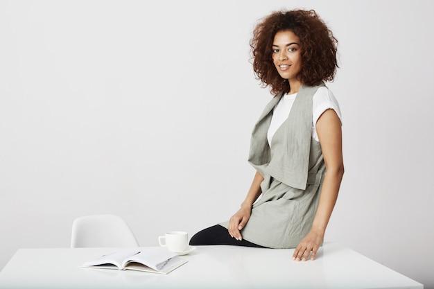 Femme d'affaires africaine souriant assis sur une table au lieu de travail sur un mur blanc.