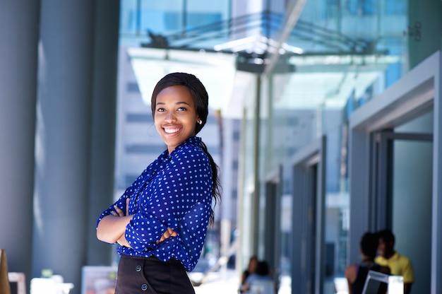 Femme d'affaires africaine souriante avec bras croisés