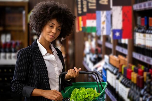 Femme d'affaires africaine tenant des bouteilles de vin dans un supermarché.